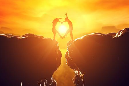 Pareja feliz haciendo forma de corazón sobre precipicio entre dos montañas rocosas al atardecer. Amor concepto único. Foto de archivo