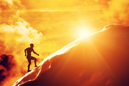 Silhouet van een man lopen op de heuvel naar de top van de berg. Trekking, actieve levensstijl, motivatie, sterkte