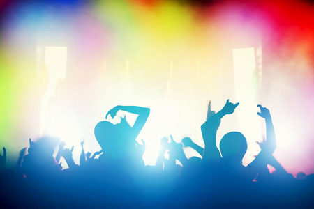 performace: Concert, disco party. People with hands up having fun in night club lights Stock Photo