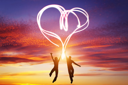 Happy couple jump together and make a heart symbol of light manifesting their love. Romantic sunset sky, Valentines Day. Stock Photo
