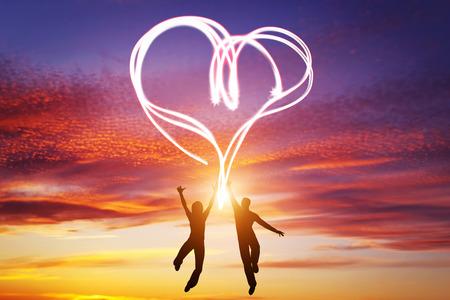 Pareja feliz saltar juntos y hacer un símbolo del corazón de la luz que se manifiesta su amor. Cielo del atardecer romántico, día de San Valentín.