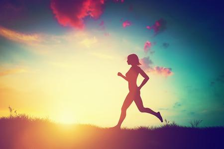 Silhouet van een fit vrouw die bij zonsondergang. Opleiding, joggen, gezonde levensstijl. Stockfoto