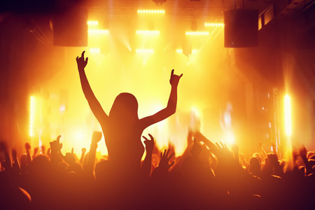 performace: Concert, disco party. Woman silhouette with hands up in foreground and people having fun in night club