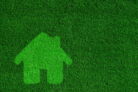 eco house: Green, eco friendly house, real estate concept. Overlay on grass background Stock Photo