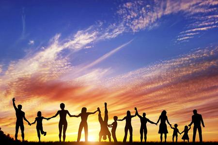 celebra: Feliz grupo de personas diversas, amigos, familia, equipo de pie juntos tomados de la mano y celebrando el �xito. Puesta de sol cielo