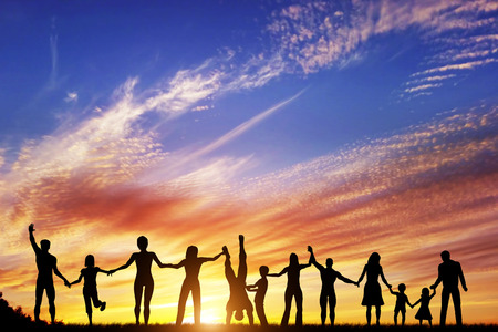 Happy group of diverse people, friends, family, team standing together holding hands and celebrating success. Sunset sky 免版税图像