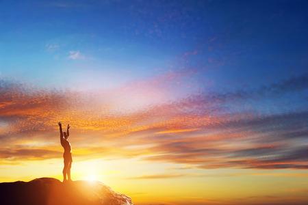 素敵な夕暮れ時、山の頂上に立って手を幸せな男。人生を楽しむ !