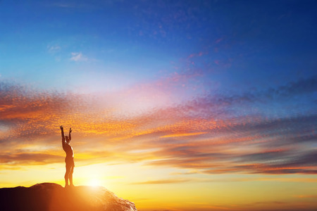 Happy man with hands up standing on the peak of the mountain at lovely sunset. Enjoy life!