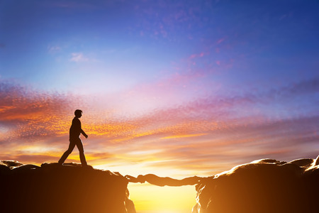 risk taking: Man walking over precipice between two mountains, another man serving as a bridge. Sunset, business conceptual