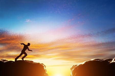 Hombre corriendo rápido para saltar sobre precipicio entre dos montañas. Conceptos de determinación, negocio, desafío, éxito, riesgo, etc.