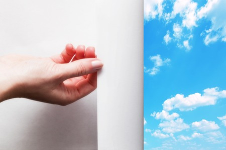 reveal: Hand pulling edge of a paper to uncover, reveal sunny blue sky.