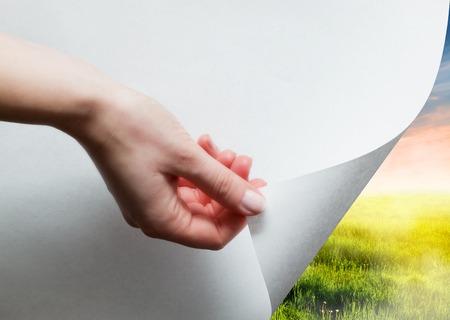 明らかに、緑の風景を明らかに下紙を引っ張る手。ページカール、概念。