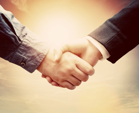 people shaking hands: Business people shaking hands against sunny sky background in vintage mood.