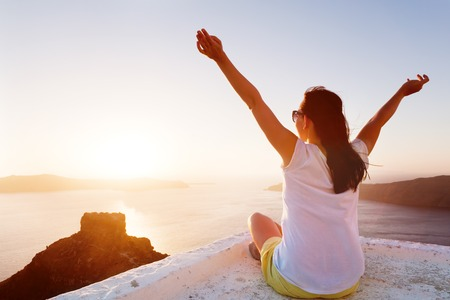 admires: Young woman sits with hands up and admires the Caldera view on Santorini, Greece. Sunset Stock Photo