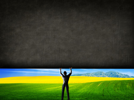 Man raising a concrete wall uncovering a new better world, green landscape. Concept.