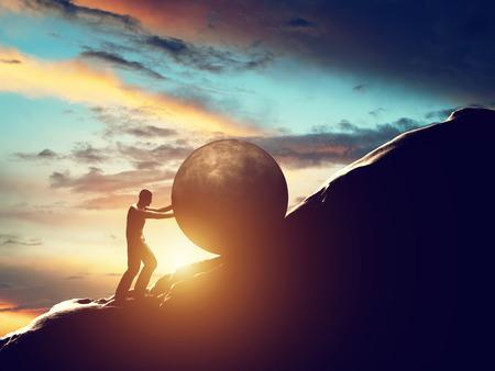 Homem que rola enorme concreto bola até a colina.