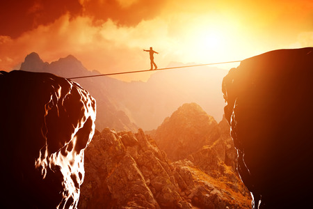 aventura: Hombre caminando y mantener el equilibrio sobre la cuerda sobre precipicio en las montañas al atardecer