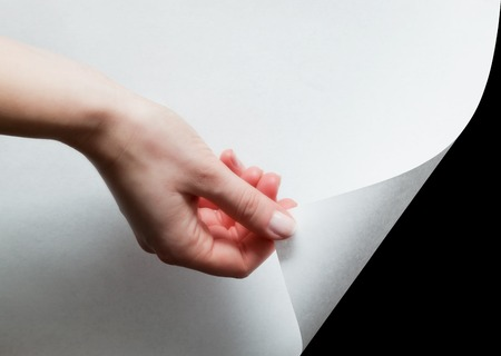 reveal: Hand pulling a bottom paper corner to uncover, reveal something. Page curl, conceptual. Stock Photo