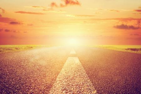 Long empty asphalt road towards sunset sun.