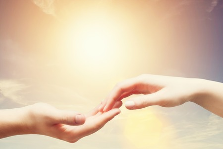 hand of god: Soft, gentle touch of man and woman against sunny sky with flare in vintage mood. Love, connection, help concepts. Stock Photo