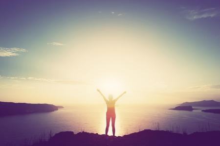 Šťastná žena s rukama stojí na útesu nad mořem a ostrovy při západu slunce.