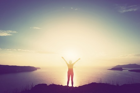 Happy woman with hands up standing on cliff over sea and islands at sunset.
