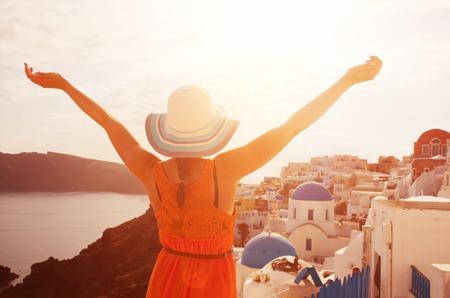Glückliche Frau in Sonnenhut freut sich über ihren Urlaub auf Santorini, Griechenland.