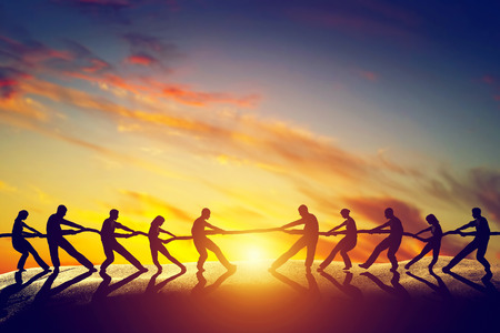 Two groups of people pulling line, playing tug of war.
