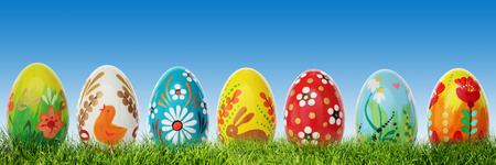 Hand painted Easter eggs on grass. Panorama, banner. Floral, colorful spring patterns and designs. Traditional, artistic and unique. photo