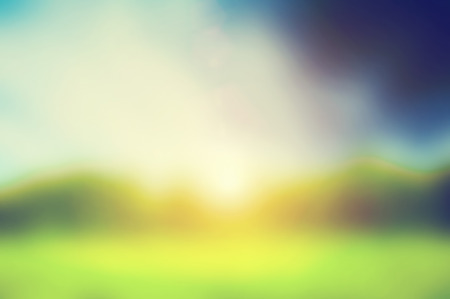 Defocused image, blur of fresh green spring summer landscape with sun shining.