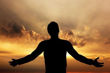 manos levantadas al cielo: El hombre orando, meditando en la armonía y la paz en la puesta del sol. La religión, la espiritualidad, la oración, la paz. Foto de archivo