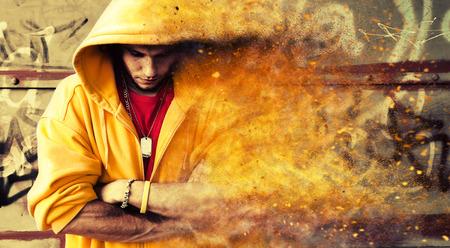 sudadera: Retrato de hombre joven en sudadera con capucha, puente en la pared de la pintada del grunge. Efecto Partículas
