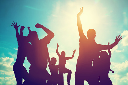 victory: Happy friends, family jumping together in a circle having fun and expressing emotions of joy, freedom, success. Silhouettes on sunny sky