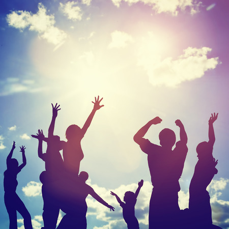 Happy friends, family jumping together in a circle having fun and expressing emotions of joy, freedom, success. Silhouettes on sunny sky