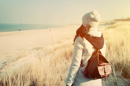 adventure holiday: Woman with retro backpack standing on the beach, dunes and looking at the sea. Vintage mood, adventure, travel