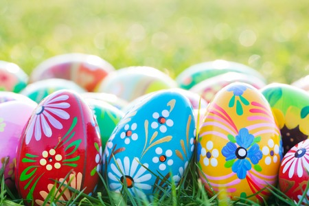 Hand-painted Easter eggs on grass. Floral, colorful spring patterns and designs. Traditional, artistic and unique. photo