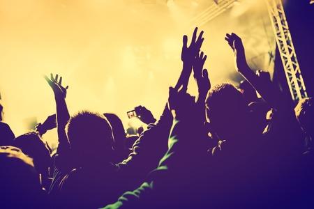 Concierto, fiesta disco. Las personas con las manos en alto que se divierten en las luces del club nocturno. Humor de la vendimia Foto de archivo