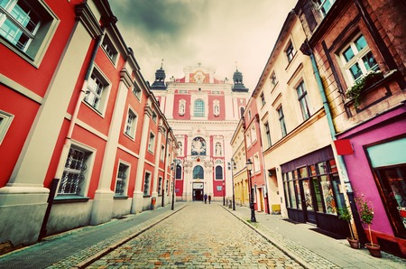 wielkopolska: Baroque Collegiate Church in Poznan, Posen, Poland. Old town street. Vintage Editorial