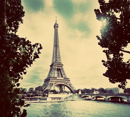 paris vintage: Torre Eiffel y del río Sena, París, Francia. Perspectiva única desde detrás de los árboles próximos a los barcos turísticos. Vendimia