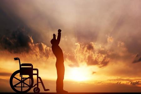 Een gehandicapte man opstaan vanuit rolstoel bij zonsondergang. Positieve concept van de genezing, herstel, medisch wonder, hoop, verzekeringen etc.