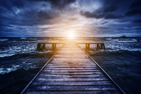stormy: Old wooden jetty during storm on the ocean. Abstract light at the end. Concept of hope, future, religion, god etc.