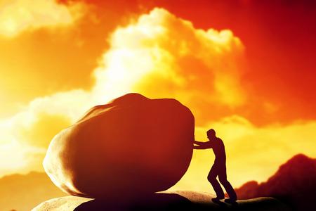 empujando: Hombre que empuja un gigante, pesada piedra, roca de la montaña. Conceptual, la lucha, tarea difícil.
