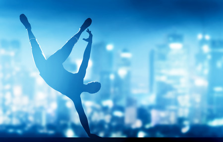 dance time: Hip hop, break dance performed by young man in city lights. Nightlife party time Stock Photo