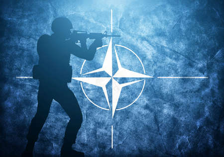 Soldier silhouette on grunge NATO flag. United army, military concept.