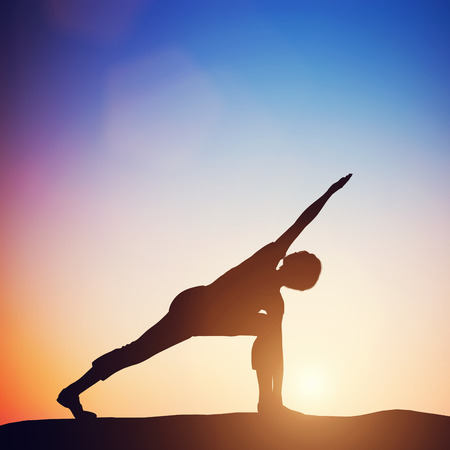 revolved: Woman standing in revolved side angle yoga pose meditating at sunset. Zen, meditation, peace