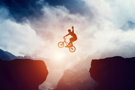 tricks: Man jumping on bmx bike over precipice in mountains at sunset. Raising hand showing hello gesture. Extreme sport, risk, cycling.