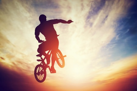 stunt: Man jumping on bmx bike performing a trick against sunset sky. Extreme sport