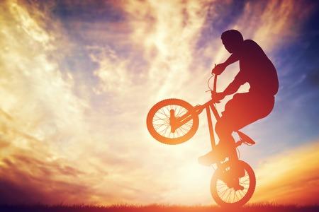 peligro: Hombre montado en una bicicleta bmx realizando un truco contra el cielo del atardecer. Deporte extremo