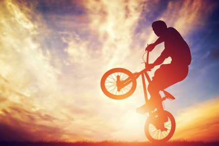 Man rijdt op een bmx fiets uitvoeren van een truc tegen zonsondergang hemel. Extreme sport Stockfoto