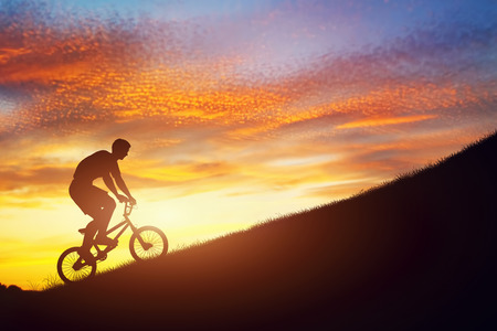 dynamic activity: Man riding a bmx bike uphill against sunset sky. Active lifestyle, motivation, strength, challenge Stock Photo